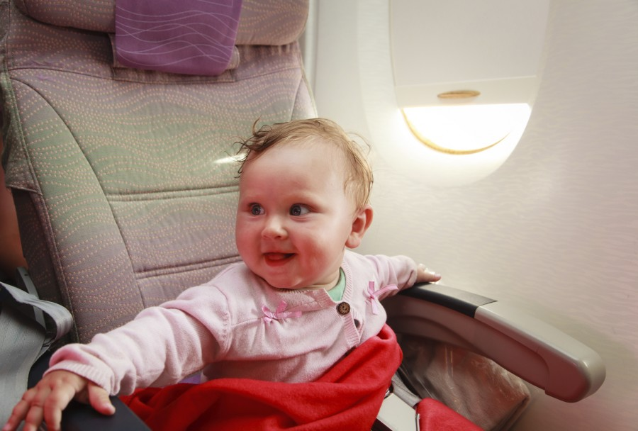 happy little girl travelling by plane
