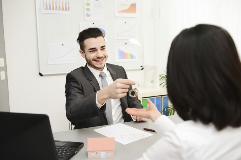 handsome young realtor in transaction with buyer at office