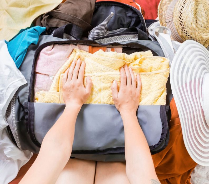 Woman trying to pack clothes in a bag