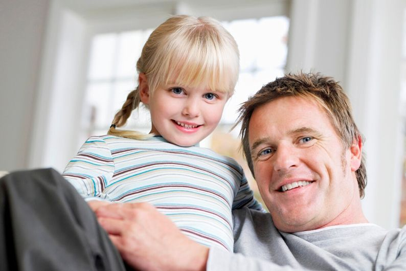 Girl Sitting On Father's Lap In House