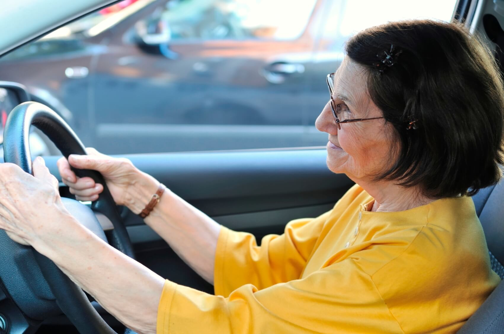 Active senior woman - grandmother driving car, detail