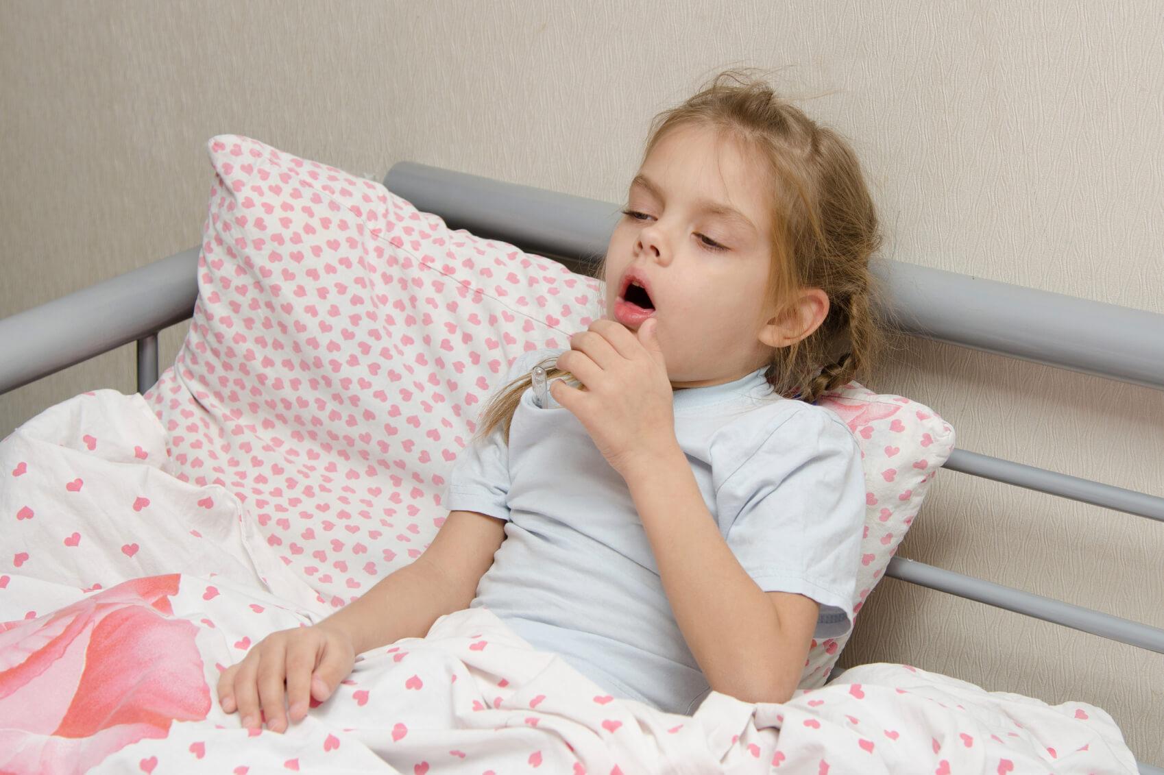 Diseased girl lying in bed coughing