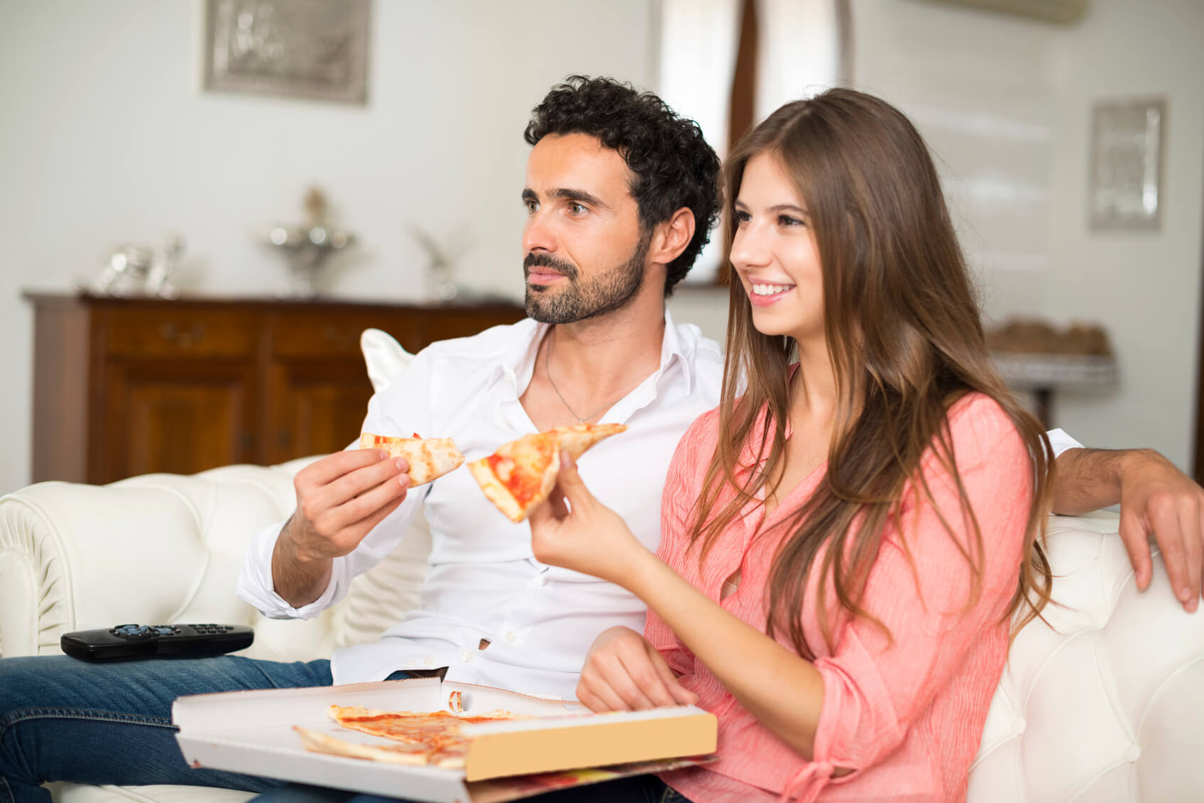 Couple watching tv and eating pizza