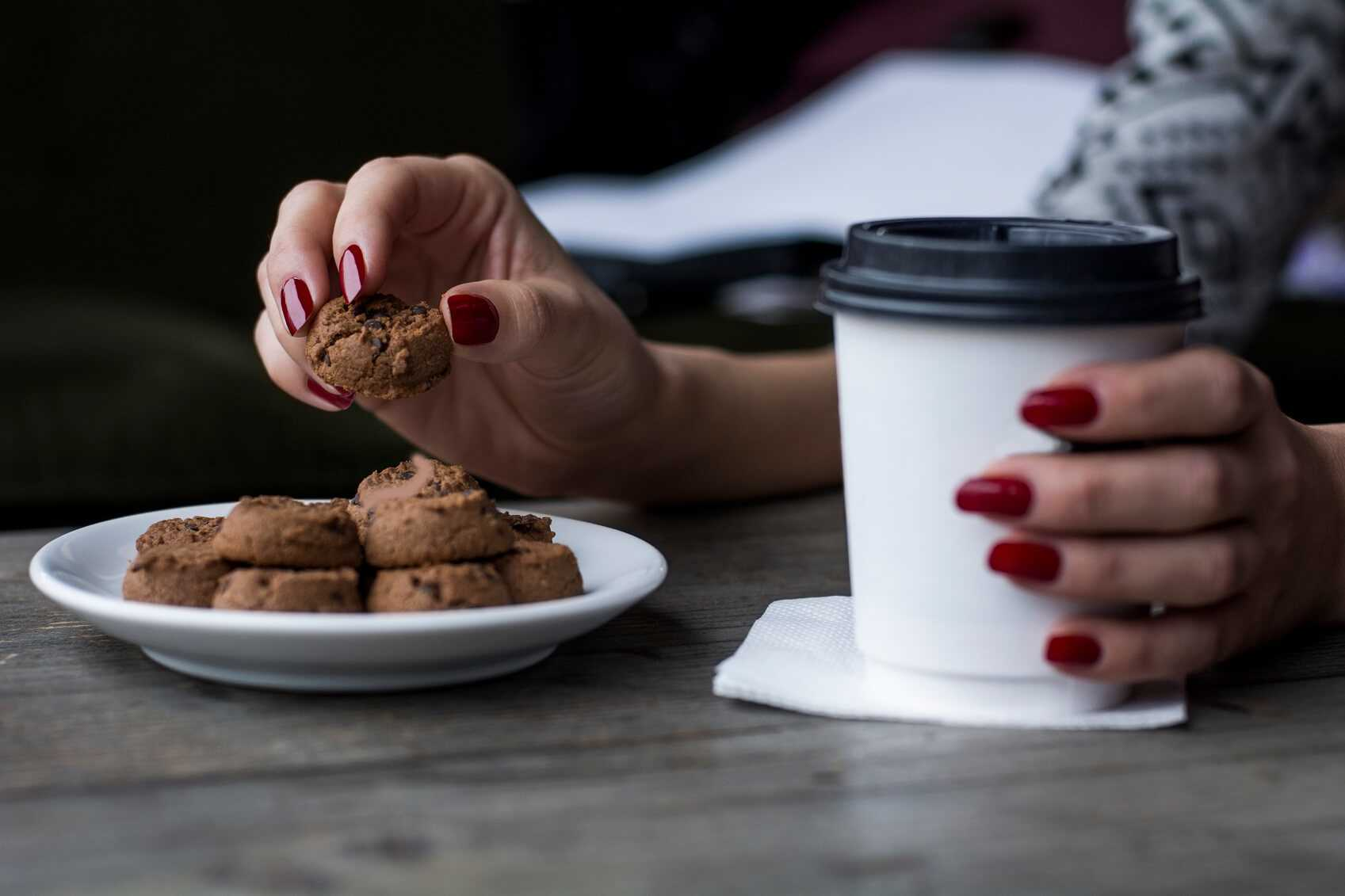 Woman's hand picking chocolate chip cookie